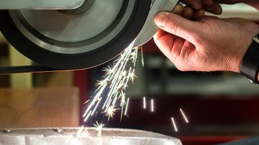 """A skilled craftsman sands the """"spine"""" of the blade to remove laser-cutting marks"""